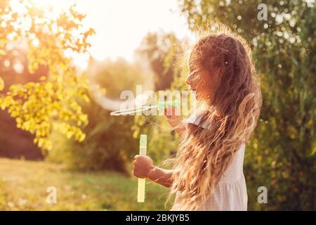 Piccola ragazza carina bolle di soffiaggio nel parco primaverile. Bambini divertirsi giocando all'aperto. Attività per bambini