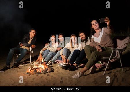 amici felici che prendono selfie al fuoco del campo sulla spiaggia