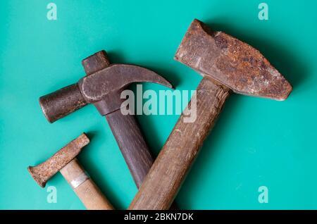 Sfondo turchese con martelli vintage. Tre vecchi martelli arrugginiti su sfondo colorato. Attrezzi manuali e manodopera. Inserire il testo. Disposizione piatta. Primo piano.