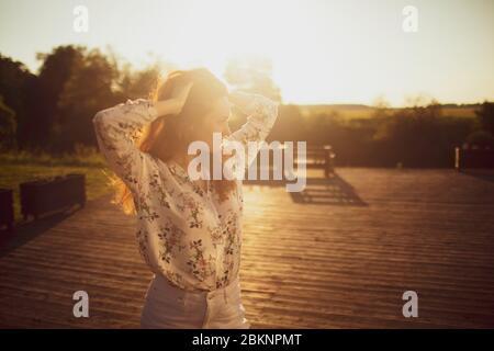 La ragazza sta godendo una giornata estiva di sole. Foto Stock