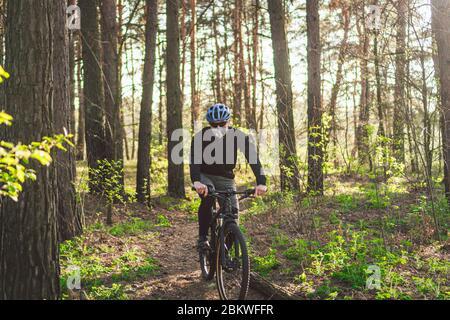 Ciclista che indossa la maschera antinquinamento. Giovane ragazzo in respiratore con filtro pm 2.5 con giro in bicicletta in parco. Covid 19 Quarantine Sport. Mountain biker equitazione Foto Stock