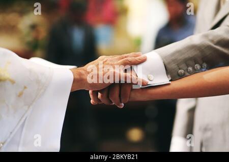 sposarsi, mani da sposa, sposo e prete in una chiesa messicana in città del messico Foto Stock