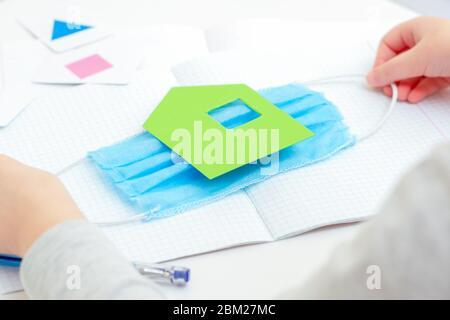 Mani per bambini che tengono una maschera protettiva medica con carta verde casa sopra il notebook della scuola sulla scrivania a casa. Concetto di apprendimento domestico.
