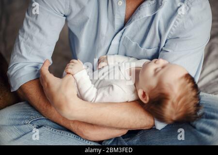 Bambino neonato che tiene il dito del genitore del padre mentre dorme. Genitore che tiene in mano il figlio dondolo in mano. Stile di vita autentico parenting paternità