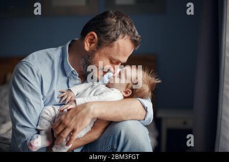 Età media padre caucasico baciare la bambina neonato addormentata. Genitore che tiene in mano il figlio dondolo in mano. Autentico stile di vita parenting fath