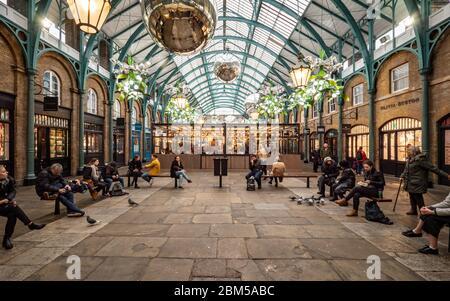 Covent Garden, Londra. Turisti e acquirenti riposano dal loro shopping natalizio in un'area con posti a sedere nel centro di Covent Garden di Londra.