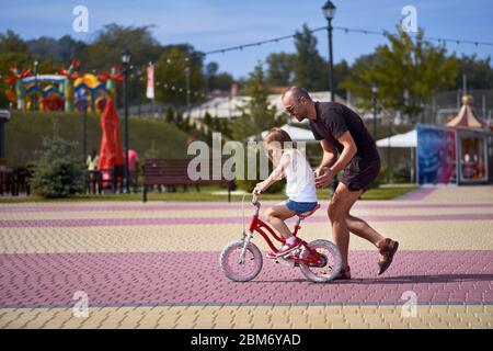 Ritratto di un padre felice premuroso che insegna alla sua piccola figlia bella che cavalcano una bicicletta in un parco verde, sorridente a tutta lunghezza Foto Stock
