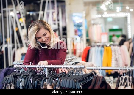Una ragazza splendida riceve una telefonata, mentre lo shopping per i vestiti Foto Stock