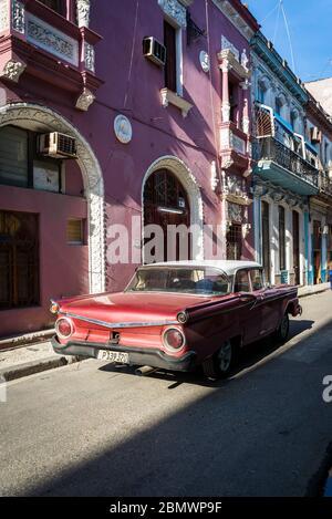 Auto d'epoca che attraversa una tipica strada stretta nel centro storico, l'Avana Vieja, l'Avana, Cuba