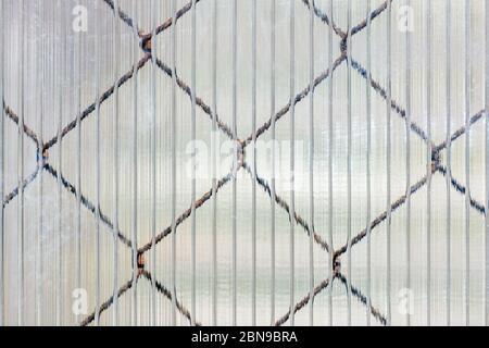 Celle di una rete di ferro che brilla attraverso la superficie cellulare di un foglio di plastica, da utilizzare come una struttura per lo sfondo.