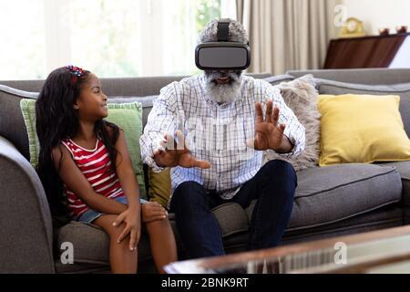 Uomo afro-americano senior e suo nipote utilizzando il visore vr Foto Stock