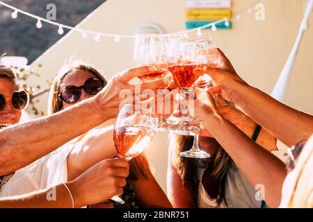 Gruppo di persone felici che tostano insieme con tazze di vino rosso sotto la luce del sole in una giornata soleggiata - attività di svago all'aperto per le donne che si divertono con bevande - vino e concetto di cantina Foto Stock