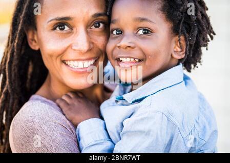 Ritratto di famiglia coppia madre e figlio nero afro razza etnica sorriso e guardare la fotocamera - concetto di diversità e mamma single con bambini piccoli - felicità e gioia concetto con amore - concentrarsi sugli occhi dei bambini