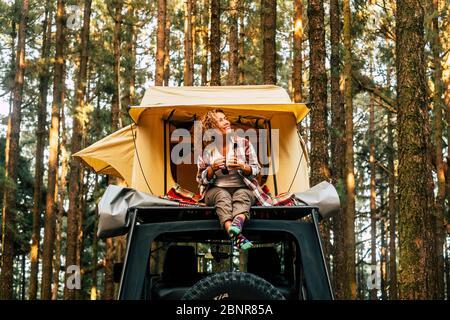 Viaggio e wanderlust stile di vita concetto con felice donna adulta solitaria sedersi sul tetto tenda auto veicolo con legno foresta in background godendo la natura e vacanze all'aperto Foto Stock