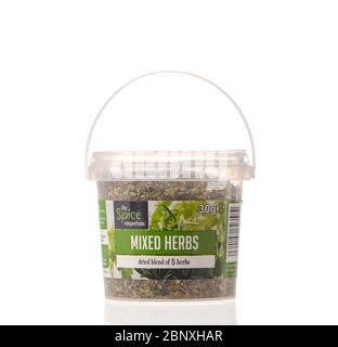 Vasca di plastica di erbe miste secche tritate dell'Emporio delle spezie isolato su uno sfondo bianco con un riflesso.