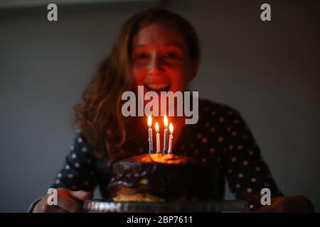 Una donna celebra il suo compleanno soffiando le candele sulla sua torta di compleanno a Belfast, Irlanda del Nord. Foto Stock