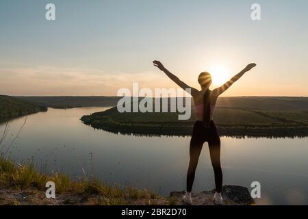 Silhouette di una giovane donna sportiva che si erge su una cresta, godendo il tramonto su una valle del fiume