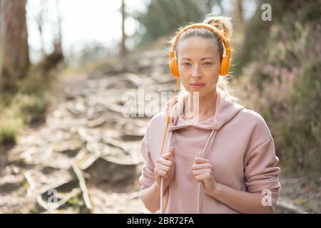 Ritratto di bella donna sportiva con felpa con cappuccio e cuffie durante la sessione di allenamento all'aperto. Foto Stock