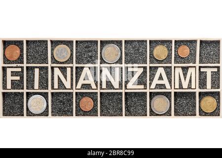 Lettere in legno compensato disposte in una scatola di raccolta con sabbia nera decorativa che rappresenta la parola FINANZA e nove monete in euro diverse in un compar adiacente