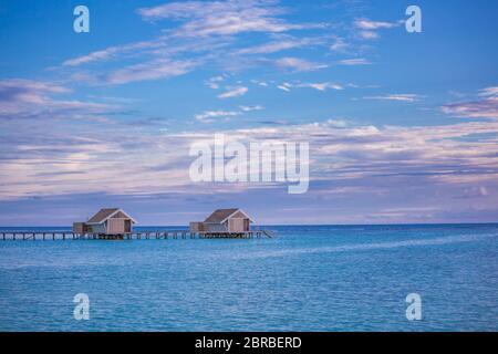 Un tramonto meraviglioso cielo e riflessione sul mare calmo, Maldive spiaggia paesaggio di lusso oltre i bungalow sull'acqua. Scenario esotico di vacanze estive e vacanze