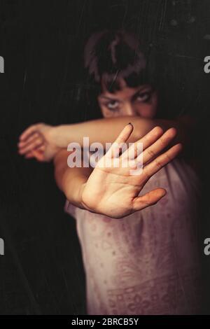 Rifiutando, violenza contro le donne. Una giovane ragazza con la mano e rifiuta la violenza di qualcuno. Lacrime e piangendo. Sfondo nero. Focus sul ha