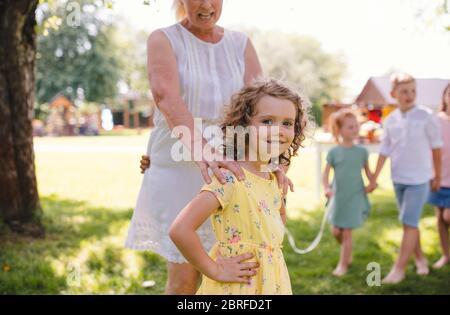 Bambini piccoli all'aperto in giardino in estate, giocare. Foto Stock