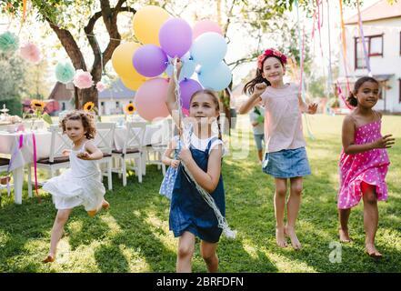 Bambini piccoli all'aperto in giardino in estate, giocando con palloncini. Foto Stock