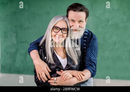 Studio di allegro ed elegante uomo bearded abbracciare la sua moglie grigia capelli affascinante dalla parte posteriore e guardando la macchina fotografica con sorriso, in piedi su grann Foto Stock