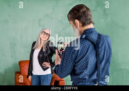 Ritratto di bell'uomo anziano che scattava foto della sua bella bella bella donna grigia con capelli che si posava a macchina fotografica e sorridente. Coppia anziana che si diverte Foto Stock