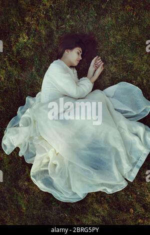 Bella donna con abito vittoriano su un letto di erba