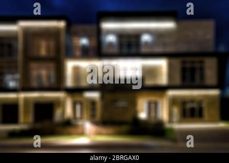 Case cittadine nella città notturna, creativo sfondo offuscato astratto con effetto bokeh Foto Stock
