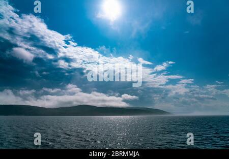 La nebbia marina che si stesa sul mare scompare sotto il sole del mattino, quasi senza vento, cieli blu Foto Stock