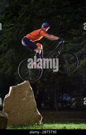 Vista frontale del ciclista che guarda nella telecamera durante un salto in bicicletta. Atleta che mantiene l'equilibrio sulla ruota posteriore della mountain bike sportiva. Concetto di stile di vita attivo.