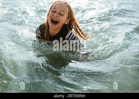 Ragazza eccitata che si diverse a nuotare in acqua di mare. Giovane ragazza seduta in acqua di mare e sorridente. Foto Stock