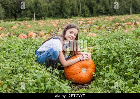 Carina bambina con zucca enorme in un tegolo di zucca. Foto Stock