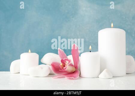 Bella orchidea, candele e pietre spa su tavolo bianco, spazio per il testo Foto Stock