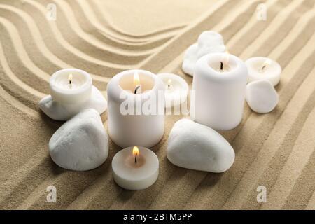 Candele e pietre su sfondo di sabbia. Concetto Zen Foto Stock