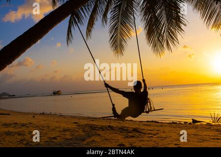 Il ragazzo gode il tramonto a cavallo su un altalena sulla spiaggia ptropicale. Silhouette di un ragazzo su un'oscillazione che pende su una palma, guardando il tramonto nel