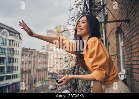 Signora allegra in piedi sul balcone e saluto amico