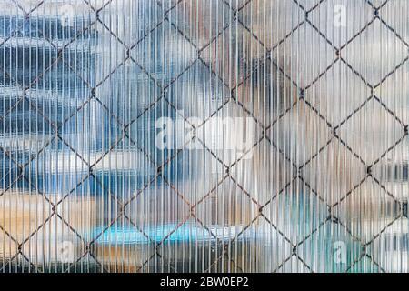 Rete di ferro che brilla attraverso la superficie di un foglio di plastica da usare come una trama per lo sfondo.