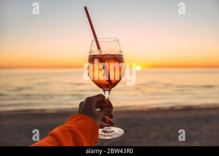 Ragazza che tiene un bicchiere di bevanda sulla spiaggia al tramonto romantico. Vetro e mano da vicino