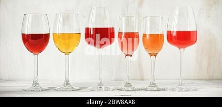 Raccolta di vari vini in un bicchiere, rosa, rosso, bianco e champagne su un tavolo rustico in legno bianco, banner. Set di vini in fila su un'annata