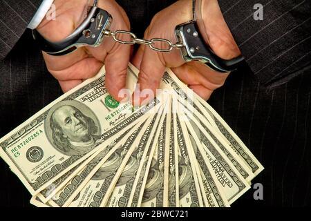 Manager mit Dollar Geldscheinen in der Hand, Hanschellen, verhaftet, Schwarzgeld,