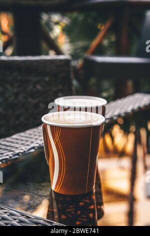 Tazze di carta con caffè in un caffè all'aperto. Incontro con gli amici, tempo all'aperto, concetto di ecologia. Immagine a toni con posizione per il testo