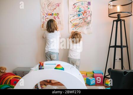 I bambini piccoli biondi giocano a dipingere a casa. Intrattenimento durante la quarantena. Famiglia a casa coronavirus. Foto Stock
