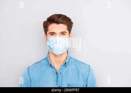 Ritratto di bel giovane uomo d'affari di successo in camicia blu indossare maschera medica di sicurezza sul viso, pandemia virus prevenzione protezione concetto