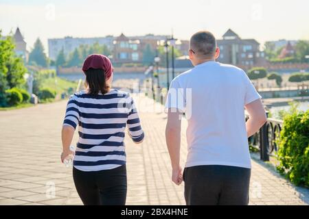 Coppia che corre in città vista posteriore, uomo maturo e donna insieme