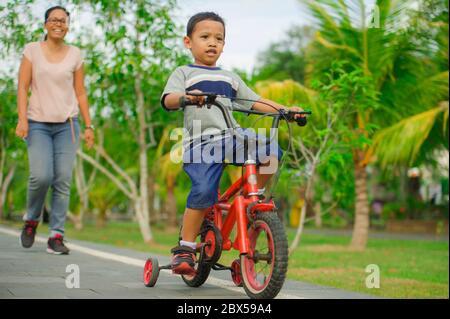 Ritratto di madre indonesiana asiatica e di bambino felice al parco della città divertendosi insieme il bambino imparando a cavalcare in bicicletta e la donna che cammina Foto Stock