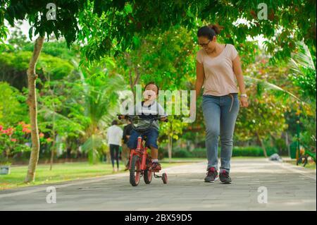Ritratto di madre indonesiana asiatica e di giovane figlio felice al parco cittadino divertendosi insieme il bambino imparando a correre in bicicletta e la donna che corre Foto Stock