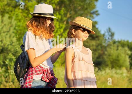 Estate, felici bambini a piedi godendo la vacanza natura, sorella più anziana treccia i suoi capelli più giovani Foto Stock
